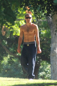 Shirtless young man walking out of a clearing