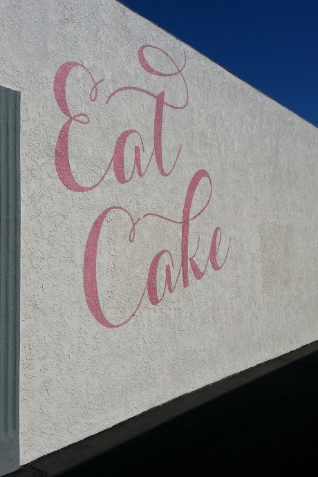 """""""Eat Cake"""" in pink script on the side of a white stucco building with an intense blue sky"""
