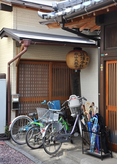 doorway in Fukuoka Japan with bicycles, umbrellas, and a paper lantern
